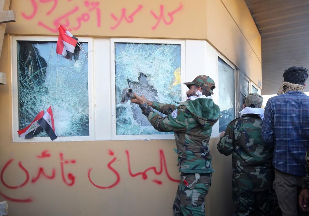 Manifestante destrói janela da embaixada dos EUA, em Bagdá, nesta terça-feira (31) — Foto: Ahmad Al-Rubaye / AFP