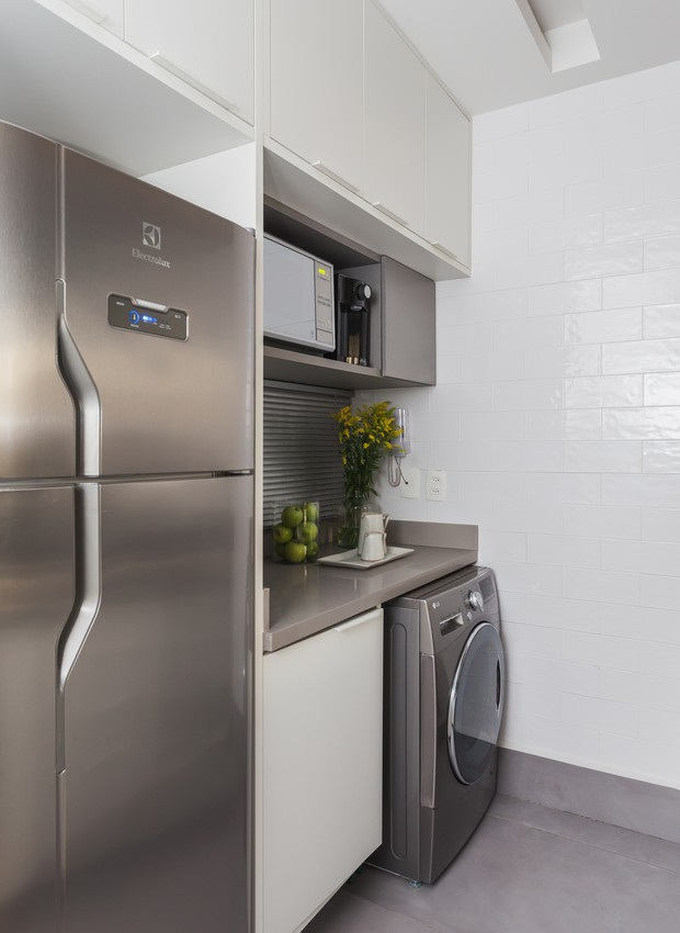 Na cozinha, todo o pé direito é aproveitado, deixando os armários nas alturas e encaixando os eletrodomésticos entre a marcenaria sob medida (Foto: Divulgação)