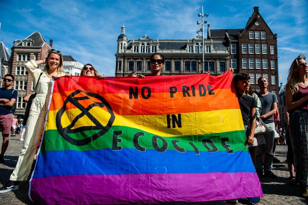 """Manifestantes da """"Extinction Rebellion"""" seguram uma bandeira com as cores do arco-íris que diz """"não há orgulho no ecocídio"""" durante protesto nas ruas de Amsterdã nesta sexta-feira (23). — Foto: Romy Fernandez / AFP"""