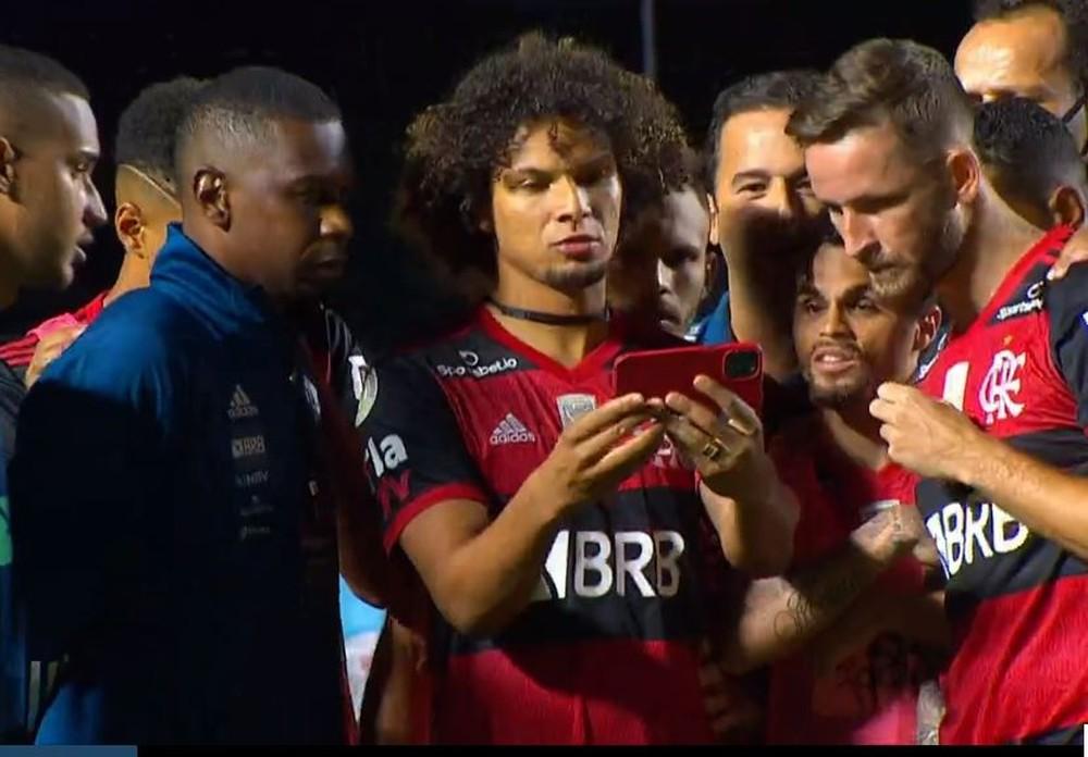 Jogadores do Flamengo assistem ao fim de jogo do Inter pelo celular, no campo do Morumbi