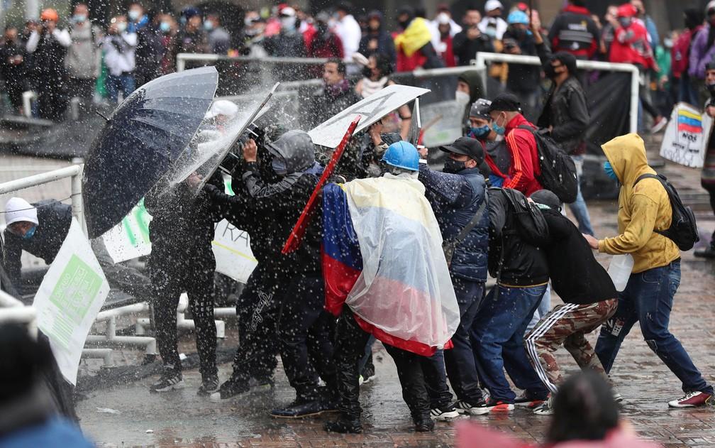 Manifestantes se protegem de canhão de água durante confronto com a polícia em Bogotá, na Colômbia, na quarta-feira (5) — Foto: AP Photo/Fernando Vergara