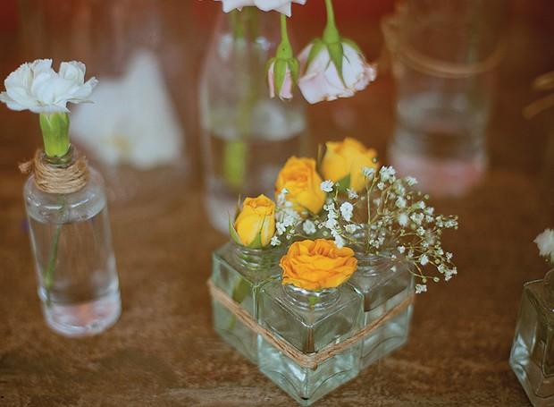 Vidrinhos diversos, destes que todo mundo tem em casa, podem virar vasos. Unidos por tiras de ráfia, os frascos ganham destaque (Foto: Tati Abreu/Editora Globo)
