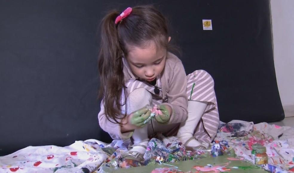 Manu pintas os quadros com as mãos misturando as tintas de variadas cores  — Foto: TV TEM / Reprodução