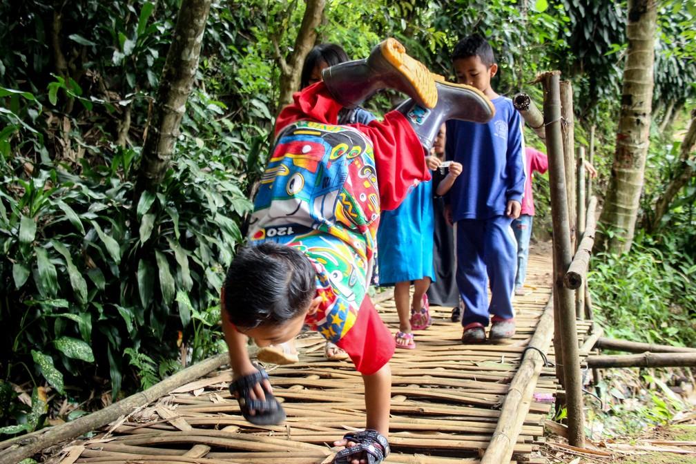 Criança com deficiência usa sandálias para proteger as mãos e conseguir chegar à escola, na Indonésia — Foto: CANTIGIE NUR FERDINAND / AFP