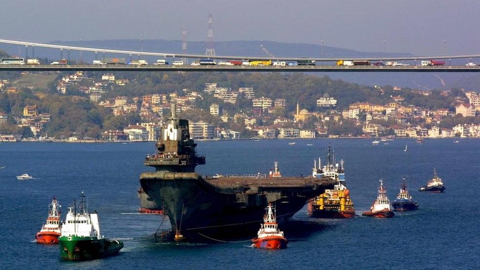 O trânsito do Varyag pelo Bósforo exigiu toda uma frota de apoio — Foto: EPA