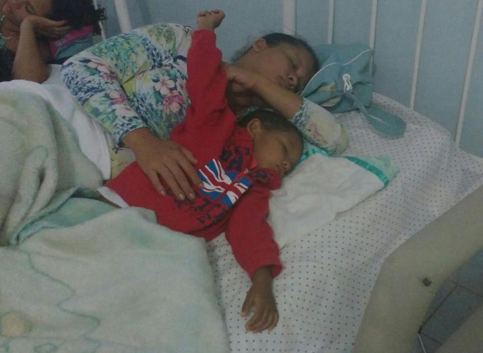Kaio, de 2 anos e 11 meses, dorme com a mãe, após sobreviver à tragéia (Foto: Juliana Peixoto/G1)