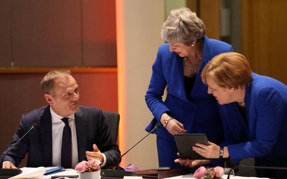 Em imagem de arquivo, as primeiras-ministras do Reino Unido, Theresa May, e da Alemanha, Angela Merkel, falam com o presidente do Conselho Europeu, Donald Tusk, antes do início de reunião do conselho, no Parlamento Europeu, em Bruxelas, na Bélgica, na quarta-feira (10) — Foto: Kenzo Tribouillard/Pool via Reuters