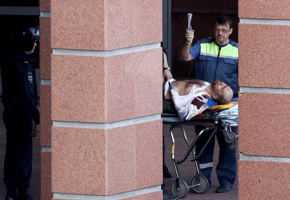 Policiais e médicos levam um ferido de maca até ambulância em frente à Corte Regional de Moscou, na Rússia. Três membros de uma quadrilha de roubo de carros russa foram mortos e dois outros foram feridos durante tentativa de fuga do tribunal no subúrbio d (Foto: Andrey Nikerichev/Moscow News Agency via AP)