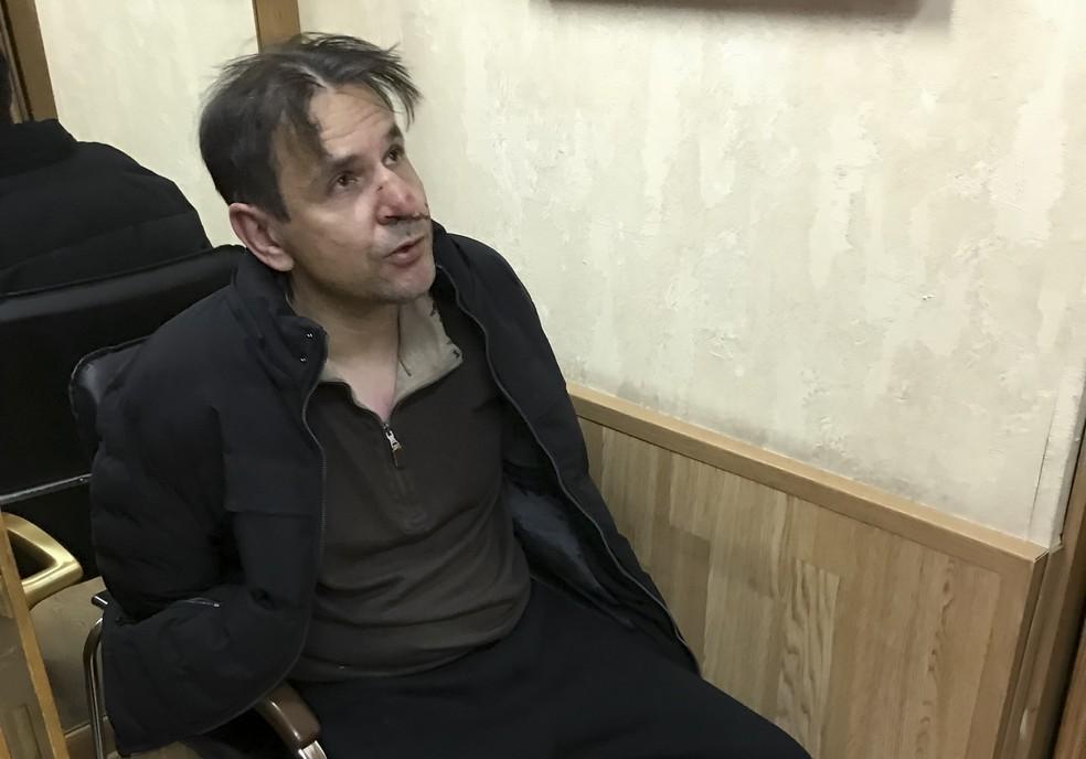 Homem indicado como o agressor da jornalista russa Tatyana Felgenhauer é detido na redação da rádio Ekho Moskvy nesta segunda-feira (23) (Foto: (Vitaly Ruvinsky, Ekho Moskvy photo via AP)