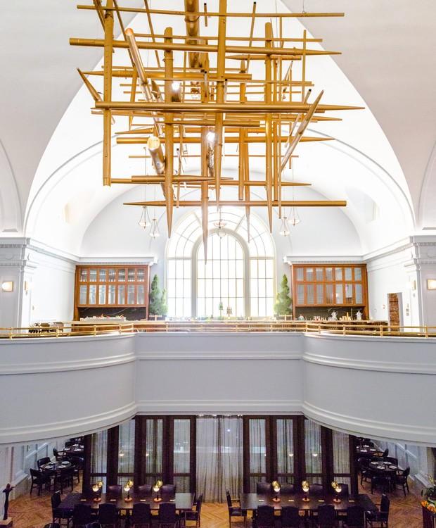 O pendente do hall de entrada foi feito a partir dos tubos retirados do órgão da antiga igreja (Foto: Deezen/ Reprodução)