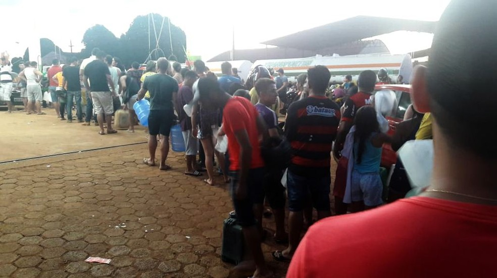 Em um dos poucos postos que ainda tem combustível em RO, moradores fazem fila com galões na mão para abastecimento (Foto: Cássia Firmino/ G1)