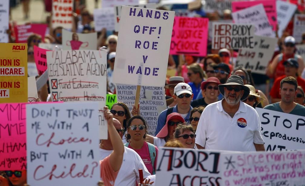 """Mulheres foram às ruas nos Estados Unidos nesta terça (21) em um protesto nacional contra as restrições ao aborto. Na foto, uma mulher segura uma placa com """"tire as mãos de Roe v. Wade"""" em Montgomery, no Alabama. — Foto: Butch Dill/AP"""