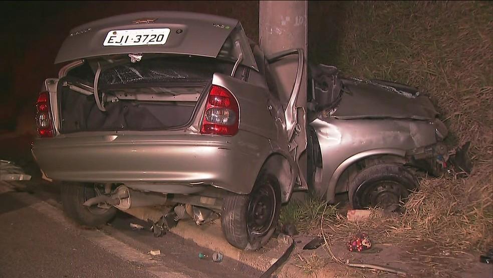 Carro ficou preso e suspenso em poste (Foto: Reprodução/TV Globo)