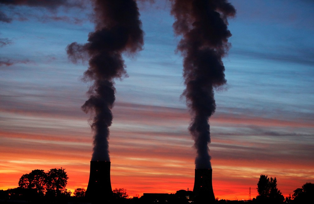 Torres de resfriamento da usina nuclear de Golfech em pôr-do-sol à beira de rio entre Agen e Tolouse, na França (Foto: Regis Duvignau/Reuters)