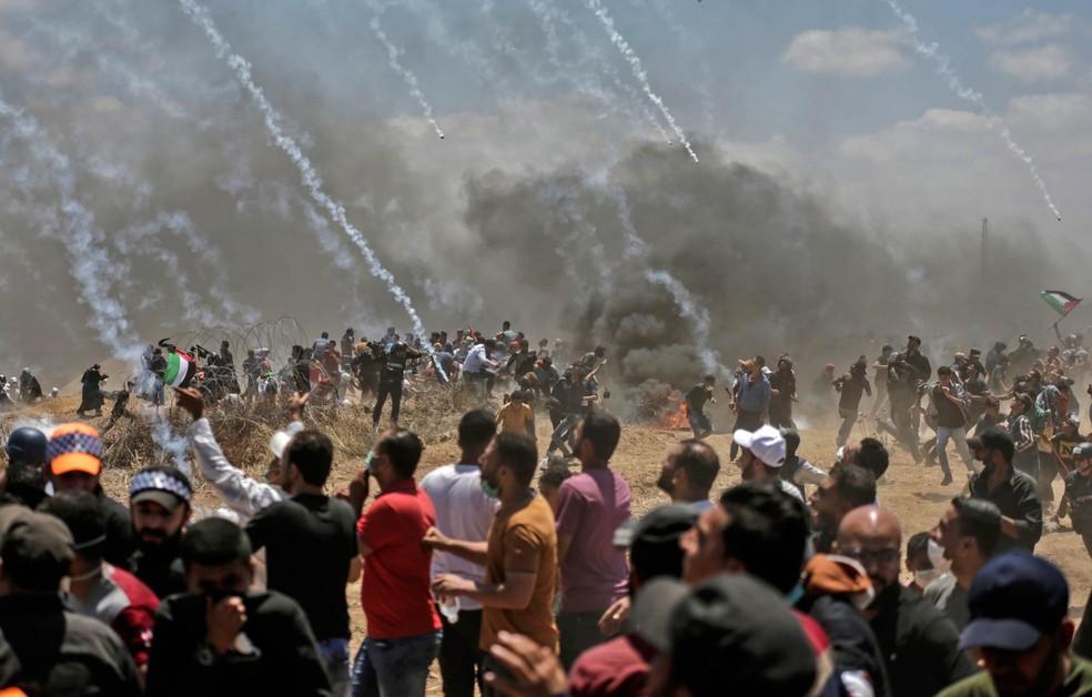 Palestinos correm para se proteger de bombas de gás atiradas por tropas israelenses na fronteira entre Gaza e Israel após protestos contra a inauguração da embaixada dos EUA em Jerusalém na última segunda-feira (Foto: Mahmud Hams/AFP)
