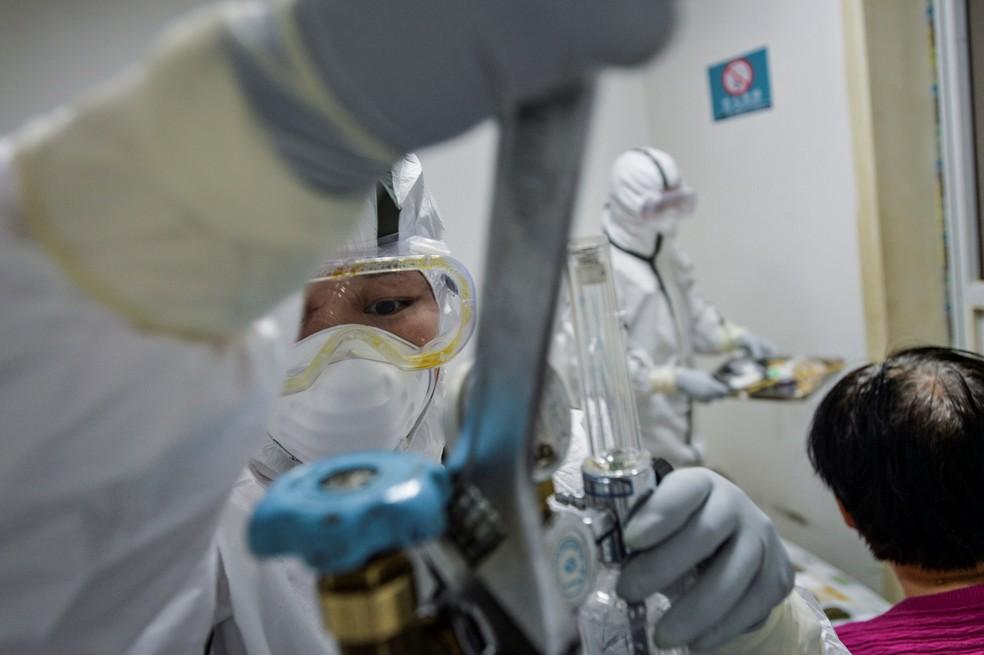 13 de fevereirio: Em meio aos cuidados de paciente com Covid-19, o novo coronavírus, profissional da saúde usa equipamentos de proteção enquanto troca o tanque de oxigênio em Wuhan, na China. — Foto: China Daily/Reuters