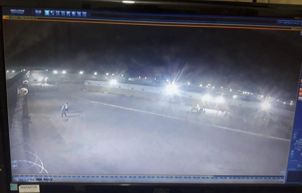 Câmeras do Complexo do Curado registraram presos pegando latas de cerveja arremessadas sobre o muro, no Recife — Foto: Reprodução/WhatsApp