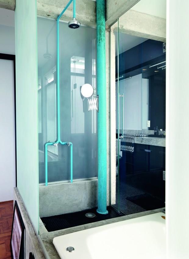 Na área do chuveiro deste banheiro, a tubulação e o cano de esgoto foram pintados de azul. O tom vibrante ganha ainda mais força na presença da estrutura de concreto (Foto: Victor Affaro/Editora Globo)