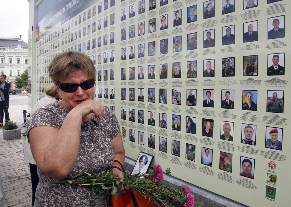 Imagem de 2017 mostra mulher que chora em um muro memorial com fotos de militares mortos no conflito com separatistas pró-russos no leste do país, em Kiev, na Ucrânia. O presidente ucraniano, Petro Poroshenko, disse que cerca de 10 mil pessoas, tanto militares como Civis, foram mortos na região de Donetsk desde 2014 — Foto: Efrem Lukatsky/AP