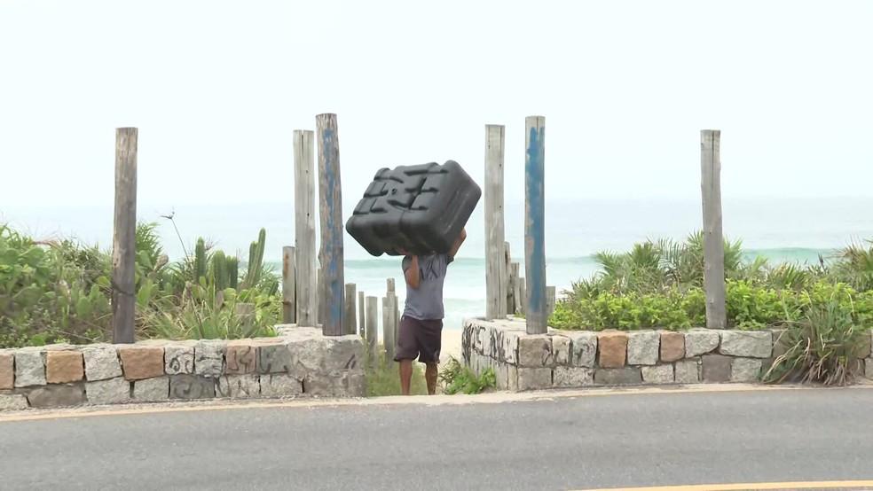 Homem carrega tanque de combustível da embarcação, que foi abandonado depois de os donos do barco perceberem a ação — Foto: Reprodução/TV Globo