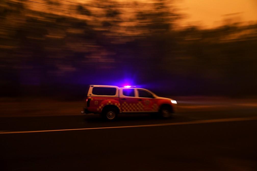 4 de janeiro - Um veículo de emergência passa pelo norte de Nowra, na Austrália, enquanto fortes ventos levam cinzas e fumaça do incêndio conhecido localmente como Currowan para Nowra, na Austrália — Foto: Tracey Nearmy/Reuters