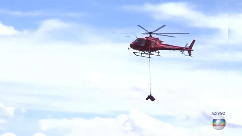 Helicóptero carrega corpo localizado em meio a lama provocada por rompimento de barragem da Vale em Brumadinho — Foto: Reprodução/TV Globo