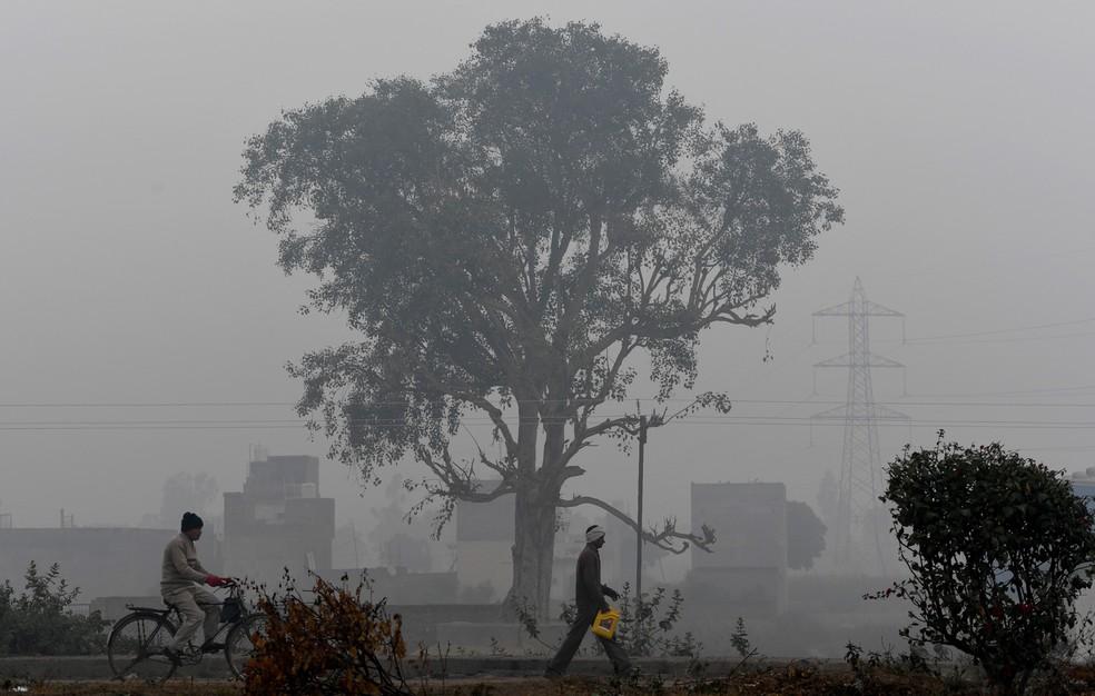 Pessoas passam em meio a condições de fumaça e neblina durante uma manhã fria em Faridabad, na Índia. Os níveis de poluição aumentam durante o inverno no norte do país, quando a qualidade do ar muitas vezes supera os níveis seguros da Organização Mundial da Saúde — Foto: Money Sharma/AFP