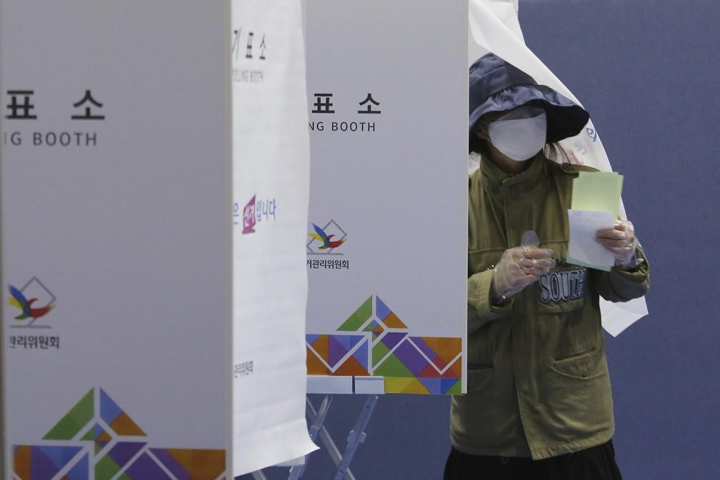 Eleitora vota em eleições legislativas na Coreia do Sul com máscaras e luvas nesta quarta-feira (15) — Foto: Ahn Young-joon/AP Photo