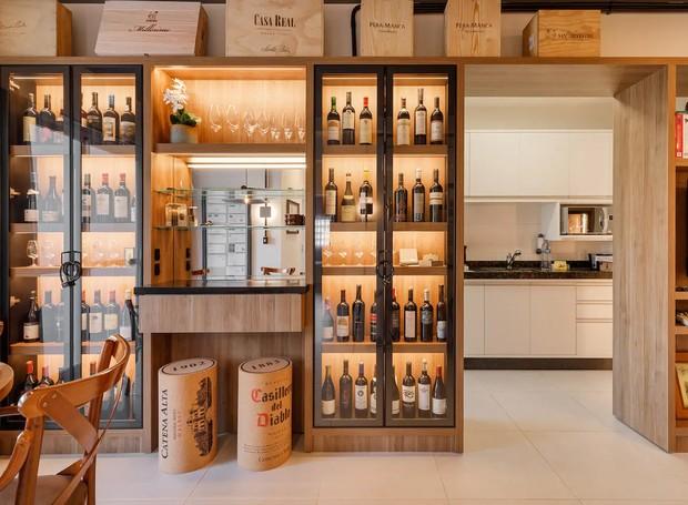 A parede dos vinhos dá acesso à cozinha, onde a passagem é livre para a área de jantar (Foto: Airbnb/ Reprodução)