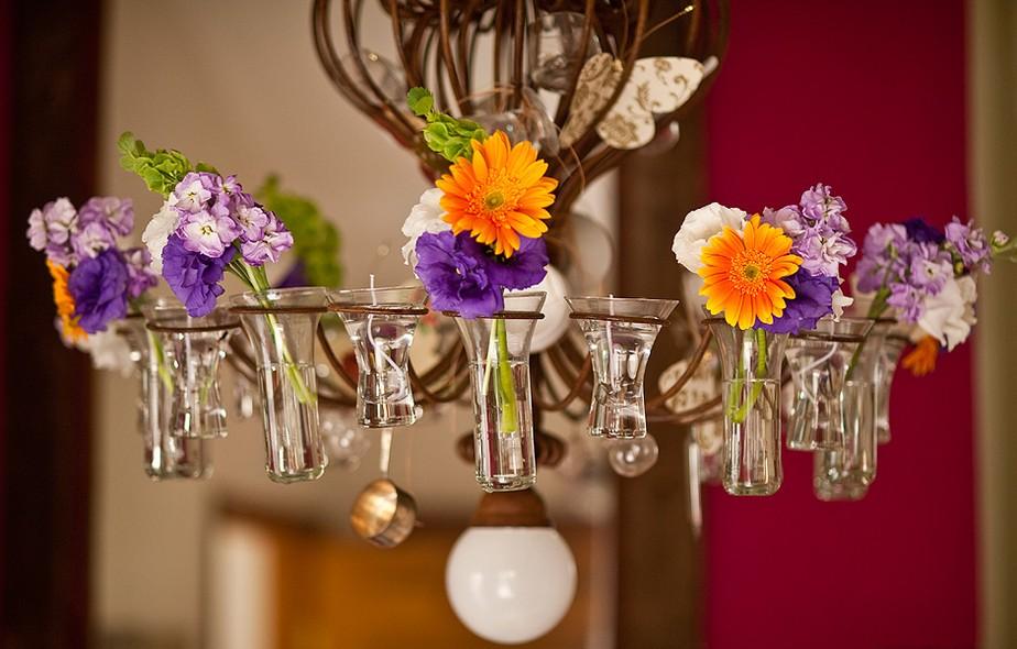 O lustre de ferro tem recipientes para velas, que funcionam como vasinhos de flores. Mas Claudia, da Calle Florida, dá uma alternativa prática: com fio de náilon ou ganchinhos feitos com arame, pendure na sua luminária garrafinhas de leite de coco