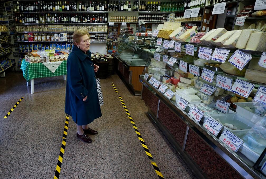 Cliente em loja no bairro de Trastevere, em Roma, respeita faixas colocadas em loja para demarcar a distância que as pessoas devem manter umas das outras para reduzir risco de contágio por coronavírus — Foto: Guglielmo Mangiapane/Reuters