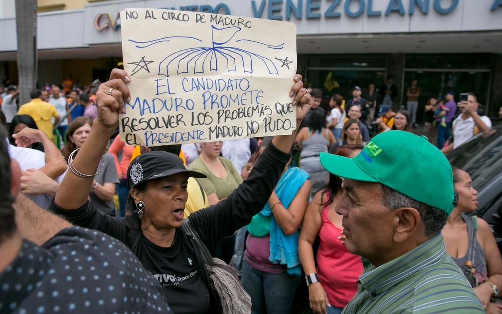 """Mulher carrega um cartaz com a mensagem 'Não ao circo de Maduro. O candidato Maduro promete resolver os problemas que o presidente Maduro não pode"""" durante protesto contra as eleições presidenciais em Caracas, na Venezuela, na quarta-feira (16) (Foto: AP Photo/Ariana Cubillos)"""
