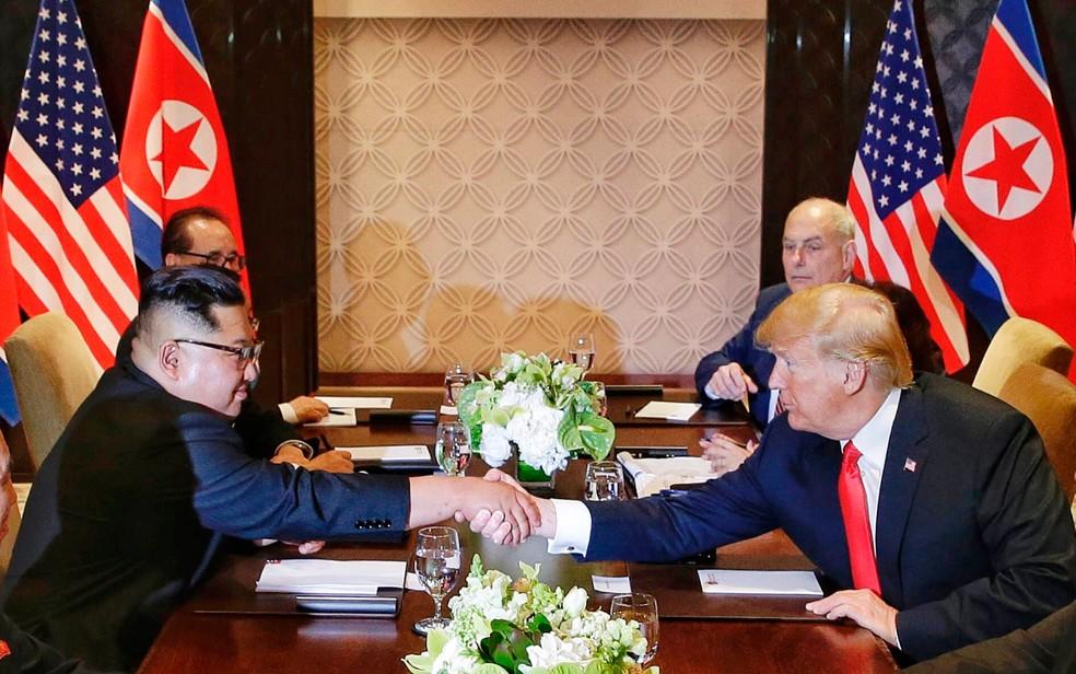 -  Kim Jong-Un e Donald Trump se cumprimentam durante reunião ao lado de assessores, em Singapura, na terça-feira  12   Foto: Kevin Lim/The Straits Time