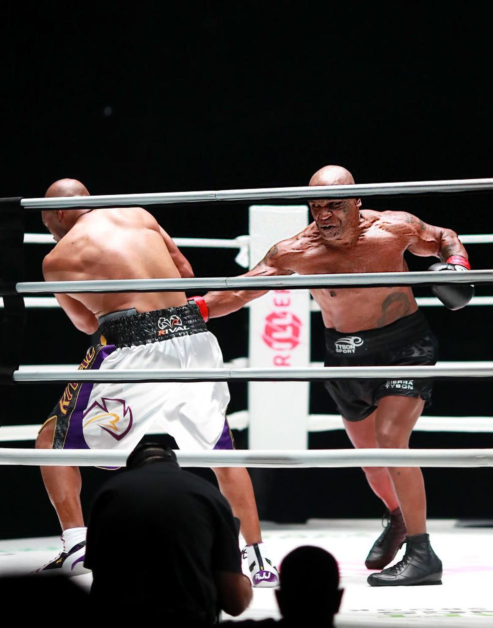 Mike Tyson tenta acertar golpe em Roy Jones Jr. — Foto: Joe Scarnici/Getty Images for Triller