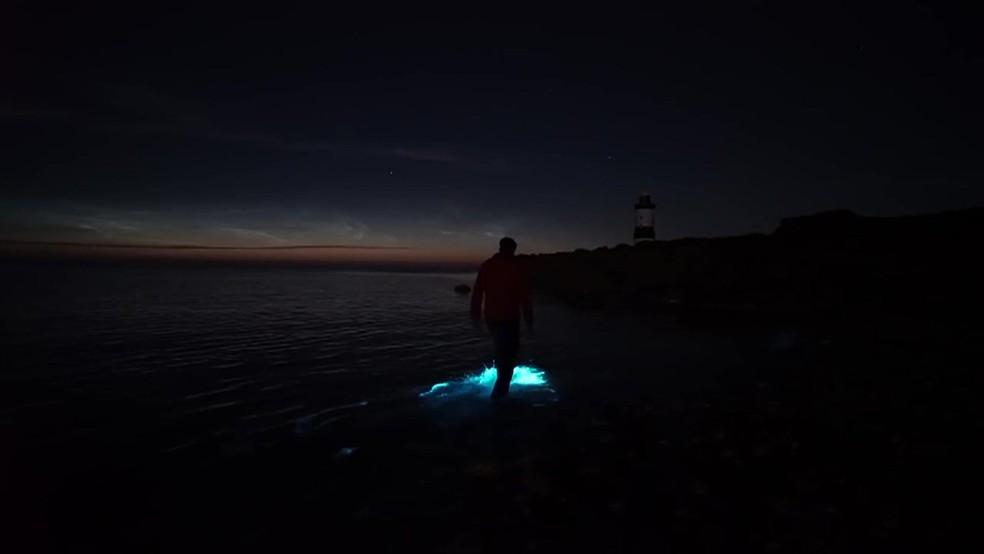 Homem andando sobre a água e destacando plânctons bioluminescentes — Foto: BBC