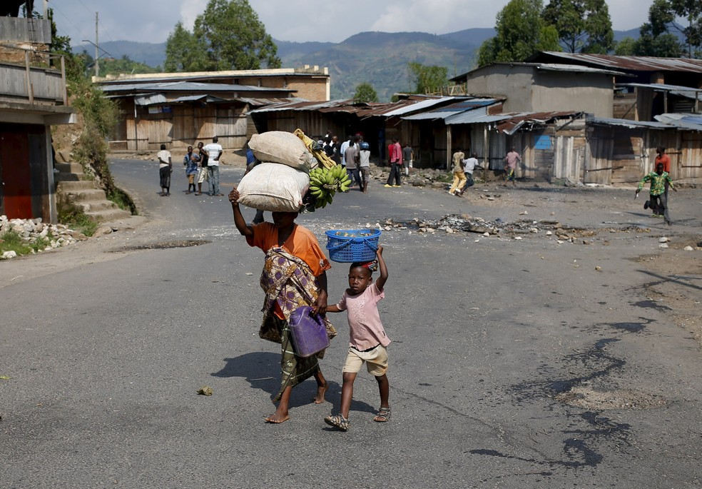 Mulher caminha com um menino por uma vila perto de Bujumbura, no Burundi (Foto: Goran Tomasevic/Reuters)