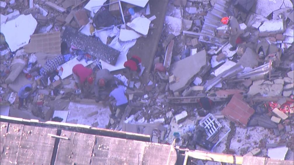 Bombeiros vasculham escombros de prédios que desabaram na comunidade da Muzema — Foto: Reprodução/ TV Globo