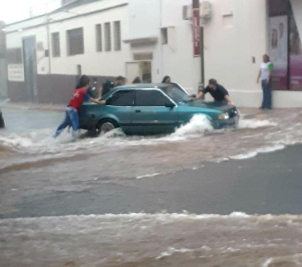 Moradores se juntaram para segurar carro em enxurrada na região da rua Caingangues, em Tupã — Foto: TupãCity/Divulgação