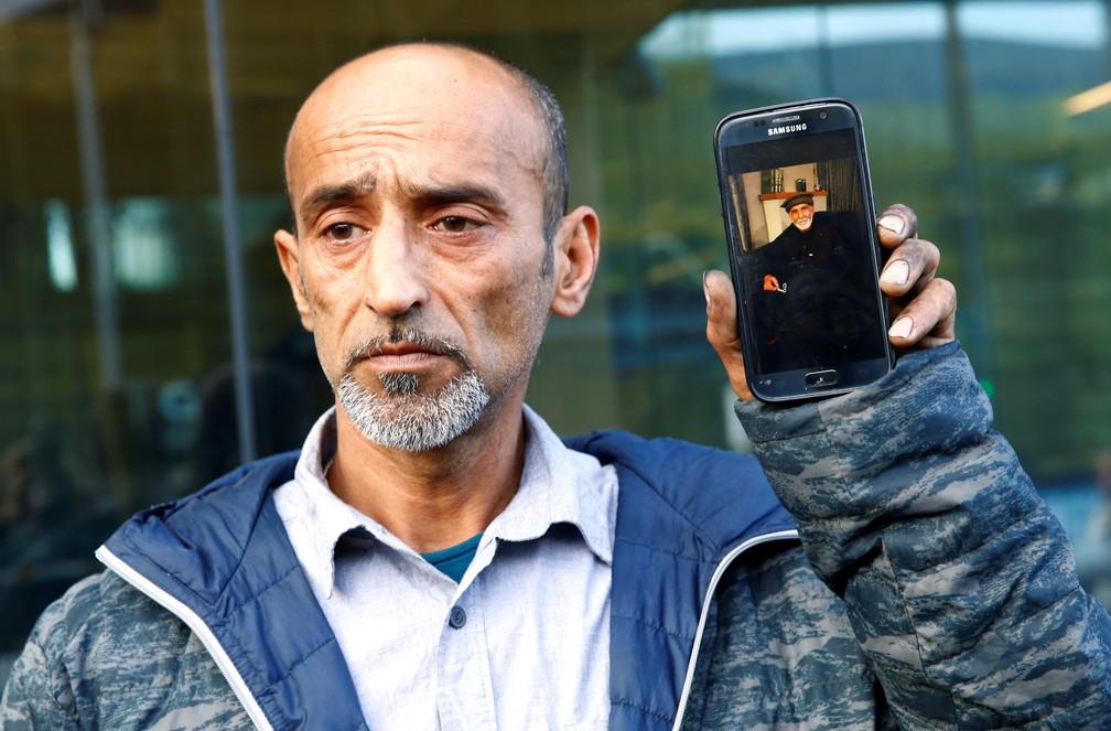 Omar Nabi mostra foto do pai, Haji Daoudi, vítima de atentado em Christchurch, Nova Zelândia, neste sábado (16) — Foto: Edgar Su/Reuters