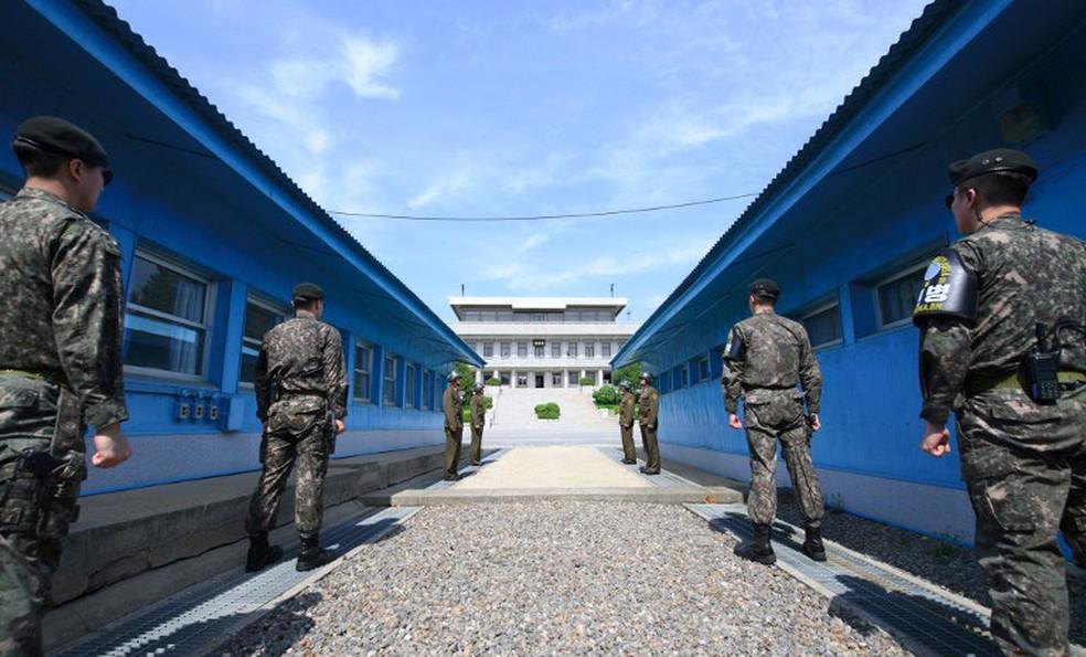 -  Soldados sul e norte-coreanos fazem segurança na linha que faz fronteira entre as duas Coreias, na zona desmilitarizada de Panmunjom  Foto: Korea Sum
