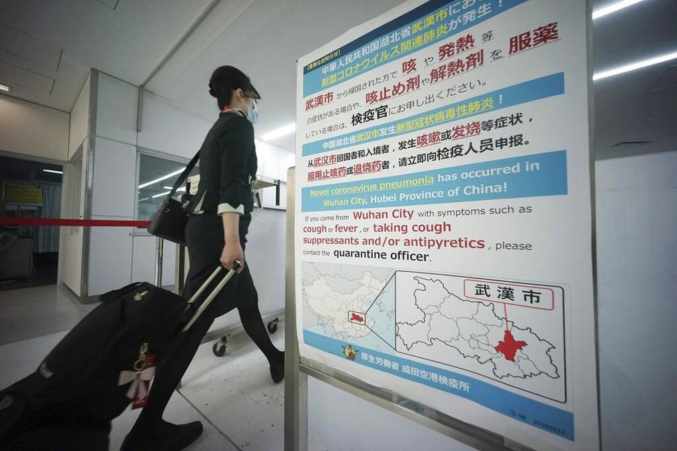 Uma comissária de bordo passa por scanners de temperatura corporal e um quadro de avisos sobre coronavírus no aeroporto internacional de Narita, perto de Tóquio, na quinta-feira (23) — Foto: Eugene Hoshiko/AP
