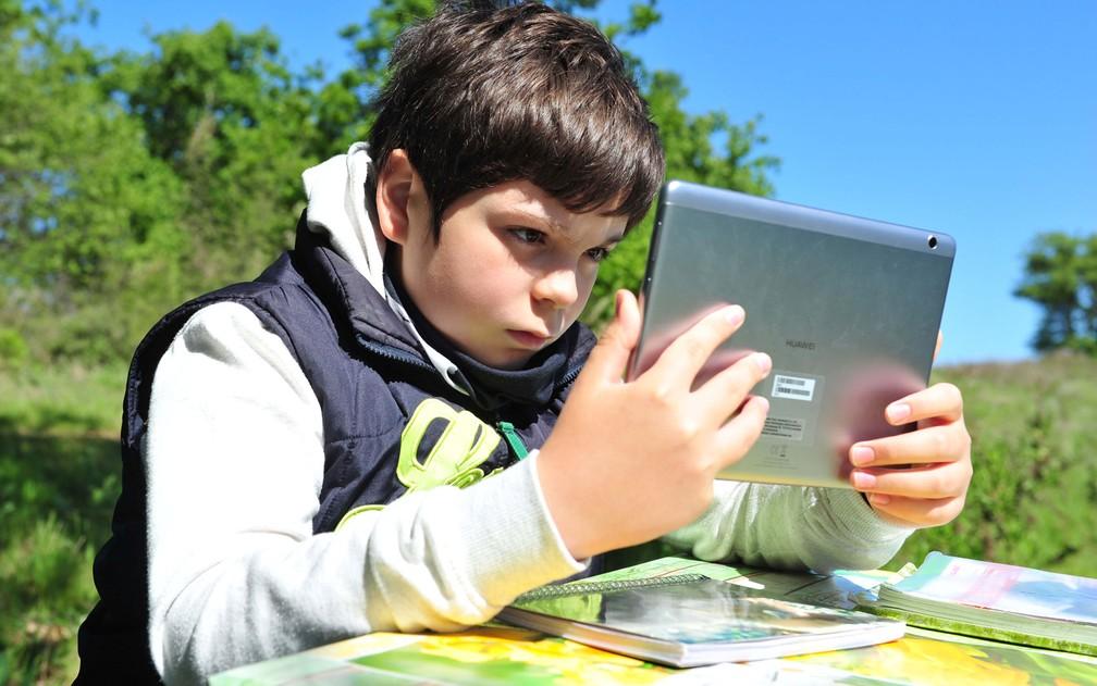 Giulio Giovannini, de 12 anos, é obrigado a ir até o campo, a 1,5 km de sua casa, para conseguir acessar internet e estudar, em Scansano, na Itália — Foto: Reuters/Jennifer Lorenzini