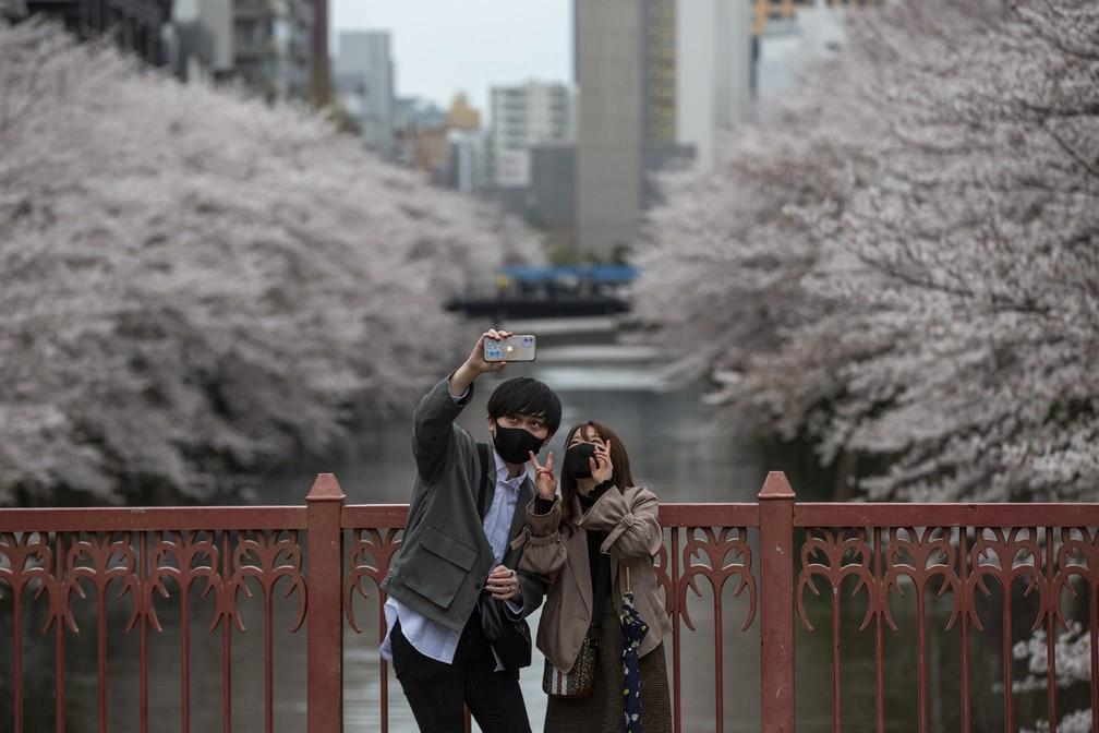 Japoneses aproveitam a florada para sair às ruas e tirar selfies sobre o rio Meguro, em Tóquio, em 28 de março — Foto: Kiichiro Sato/AP
