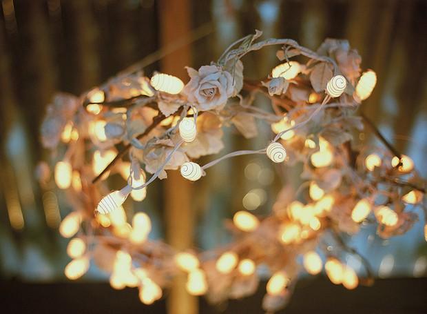 As luzinhas pisca-pisca podem fazer uma linda guirlanda para iluminar a festa. Foram usadas flores de tecido e casulos de bicho-da-seda (Foto: Tati Abreu/Editora Globo)