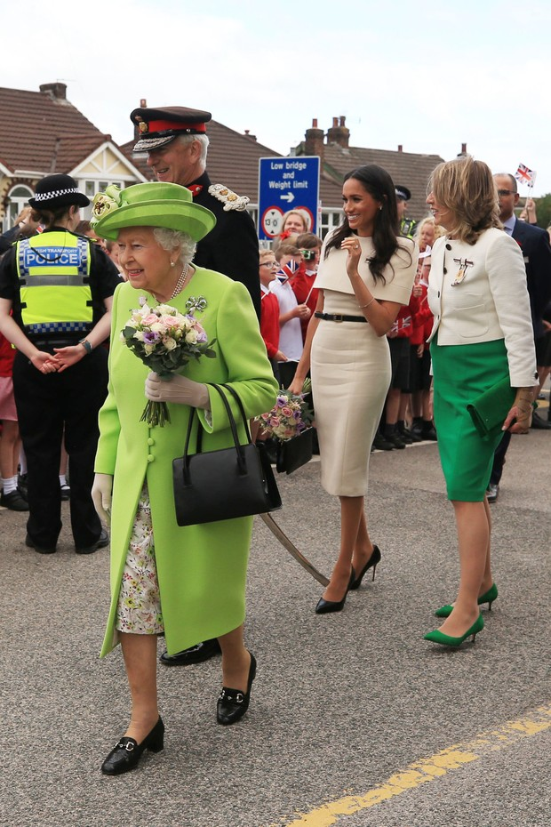 RUNCORN, CHESHIRE, ENGLAND - JUNE 14:  Queen Elizabeth II holds flowers as she and Meghan, Duchess of Sussex greet the crowds after arriving by Royal Train at Runcorn Station to open the new Mersey Gateway Bridge on June 14, 2018 in the town of Runcorn, C (Foto: Getty Images)