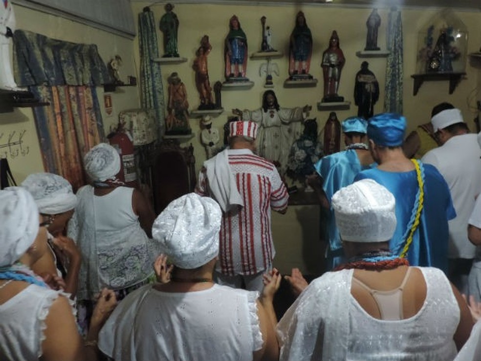 Médiuns se curvam diante de altar em terreiro de umbanda e candomblé — Foto: Carlos Dias/G1