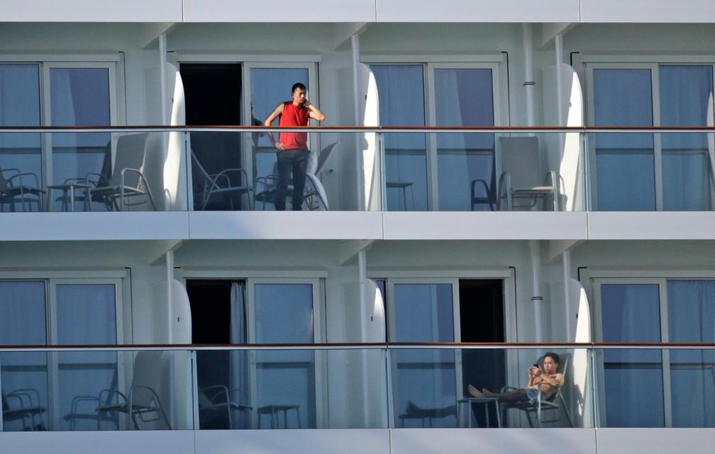 Tripulantes são vistos em suas varandas no navio Norwegian Encore, no porto de Miami, nos EUA, em 26 de março — Foto:  David Santiago/Miami Herald via AP