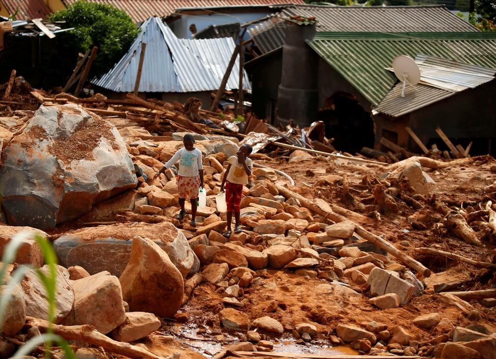 Crianças carregam água após os efeitos do ciclone Idai em Moçambique — Foto: Philimon/Reuters