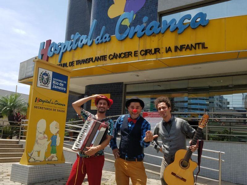 Três artistas do Macaco Prego posam na frente do Hospital da Criança