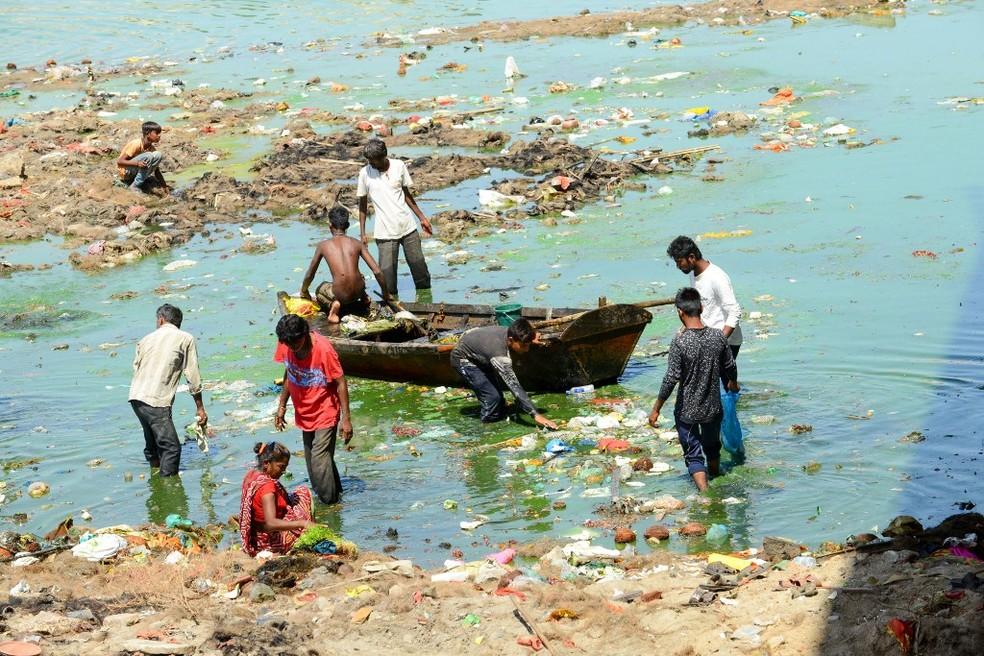 Moradores retiram lixo do rio Sabarmati, na cidade indiana de Ahmedabad — Foto: Sam Panthaky/AFP